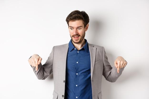 Excité mec en costume souriant et pointant les doigts vers le bas, regardant une offre spéciale avec un visage amusé