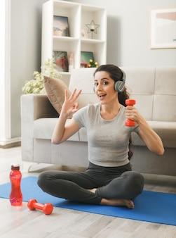 Excité montrant un geste correct jeune fille portant des écouteurs faisant de l'exercice avec des haltères sur un tapis de yoga devant un canapé dans le salon