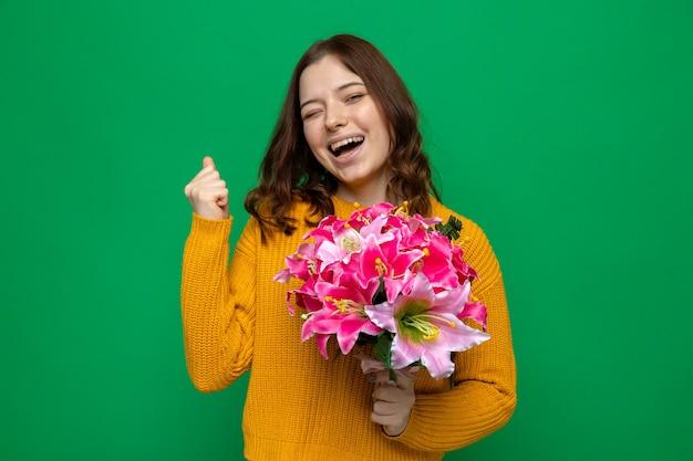 Excité montrant oui geste belle jeune fille le jour de la femme heureuse tenant un bouquet isolé sur un mur vert