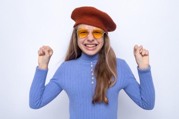 Excité montrant oui geste belle petite fille portant des lunettes avec chapeau isolé sur mur blanc