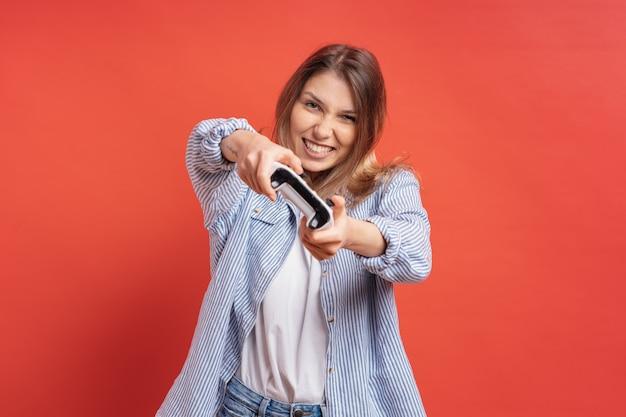 Excité occasionnel jeune femme jouant à des jeux vidéo s'amuser sur rouge