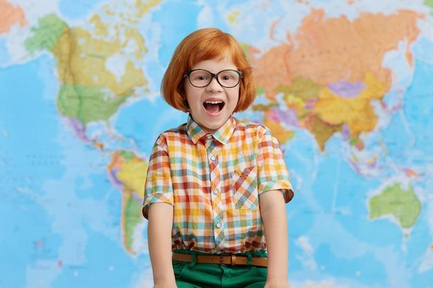 Excité petit garçon aux cheveux roux avec de grandes lunettes et une chemise à carreaux, ouvrant la bouche de joie en se tenant debout dans la salle de classe, heureux de voir ses parents et de rentrer à la maison. petit enfant intelligent
