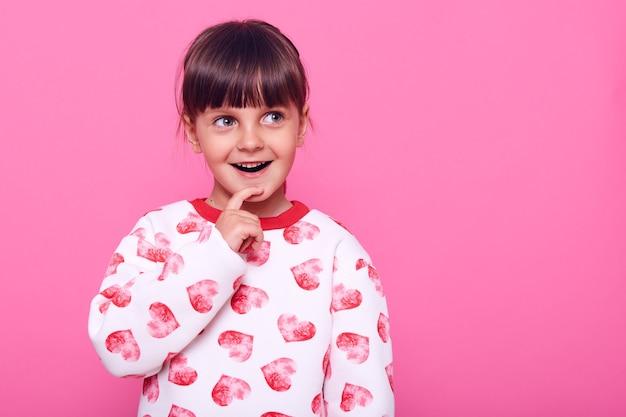 Excité petite fille a une excellente idée, en gardant le doigt sur son menton, en détournant les yeux avec une expression heureuse, copiez l'espace pour la publicité, isolé sur un mur rose