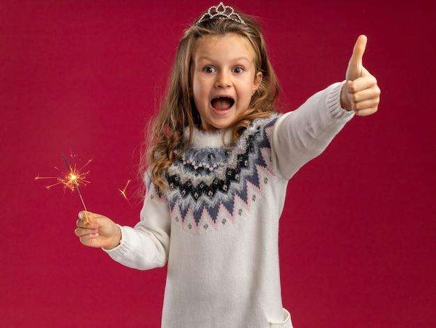 Excité petite fille portant tiare holding sparklers montrant le pouce vers le haut isolé sur mur rose