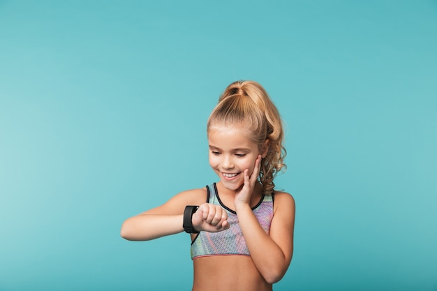 Excité petite fille portant des vêtements de sport à l'aide de smart watch isolé sur mur bleu