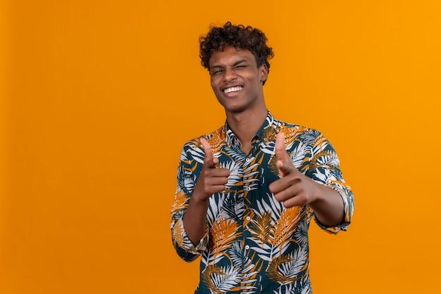 Excité et positif jeune bel homme à la peau foncée avec des cheveux bouclés en chemise imprimée de feuilles heureusement tout en pointant la caméra avec deux doigts