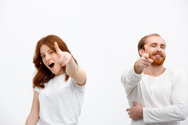 Excité rousse homme et femme pointant à l'avant