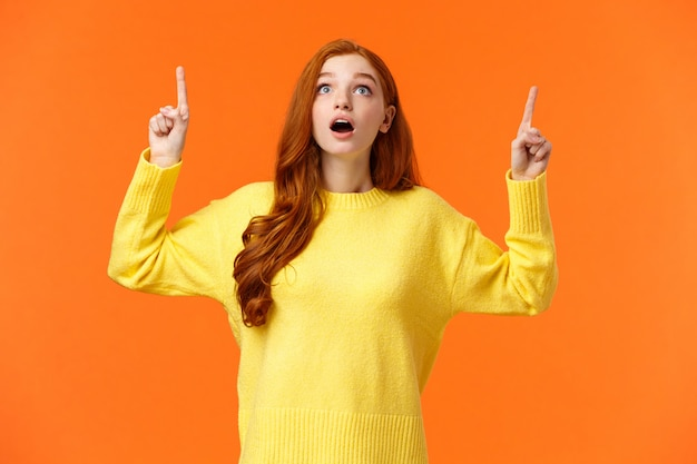 Excité, sans voix et surpris femme rousse étonnée voir la promo de vente