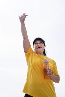 Excité senior woman dire bonjour l'eau potable après l'entraînement en plein air sur le terrain de sport