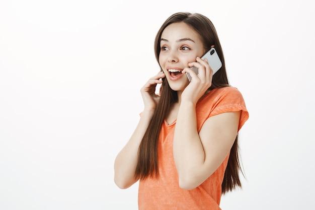 Excité souriant jolie fille parlant au téléphone mobile et à la recherche amusée