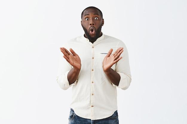 Excité et surpris jeune homme posant contre le mur blanc