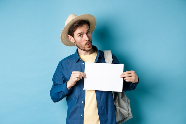 Excité touriste en chapeau de paille, faire de l'auto-stop, montrant un morceau de papier vierge et à la recherche amusée, debout sur fond bleu. copier l'espace