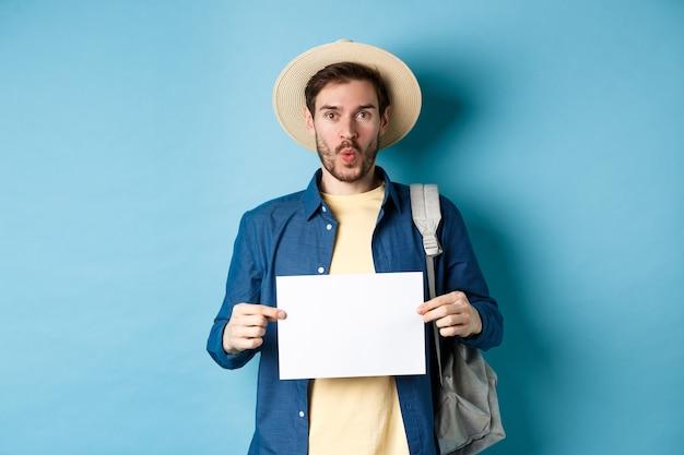 Excité touristique en chapeau de paille, tenant un morceau de papier vide et à la recherche amusée, partant en voyage d'été, debout sur fond bleu.