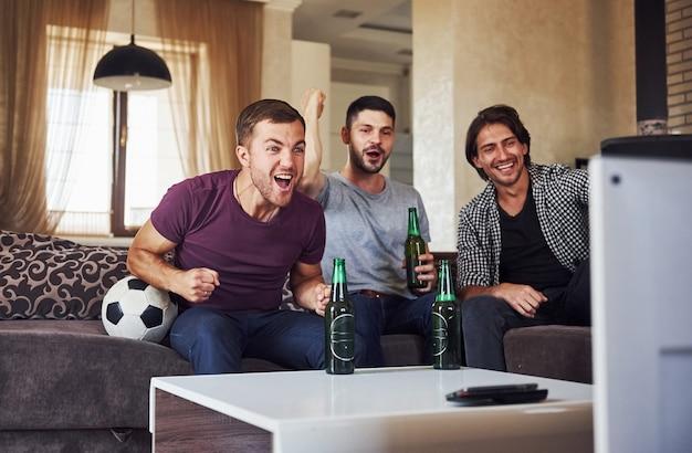 Excité trois amis regardant le football à la télévision à la maison ensemble.