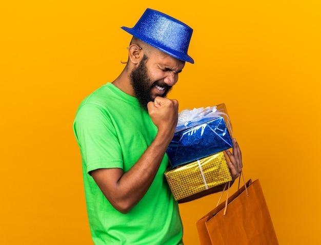 Excité avec les yeux fermés jeune homme afro-américain portant un chapeau de fête tenant des coffrets cadeaux avec un sac montrant un geste oui isolé sur un mur orange