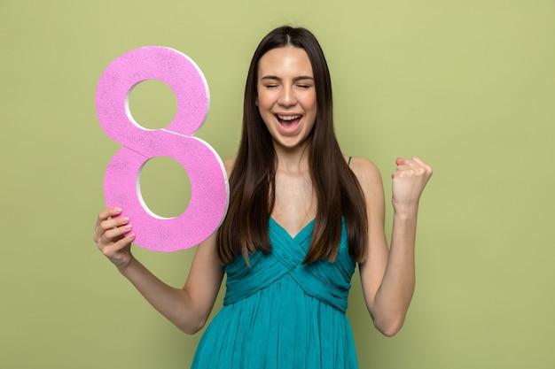Excité avec les yeux fermés montrant le geste oui belle jeune fille le jour de la femme heureuse tenant le numéro huit