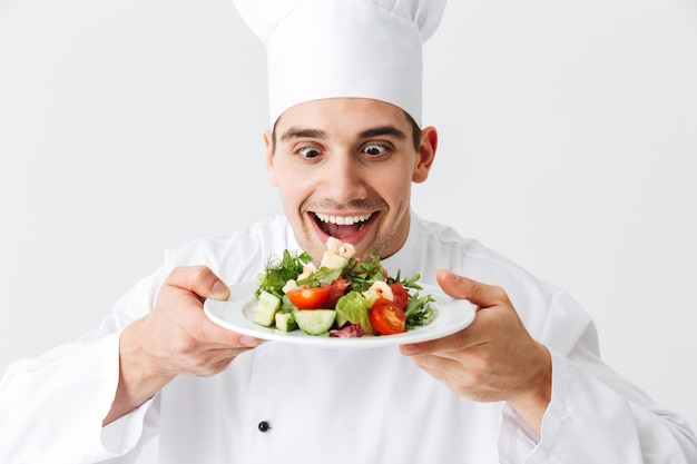 Excited man chef cuisinier en uniforme montrant salade verte fraîche sur une assiette isolée sur mur blanc
