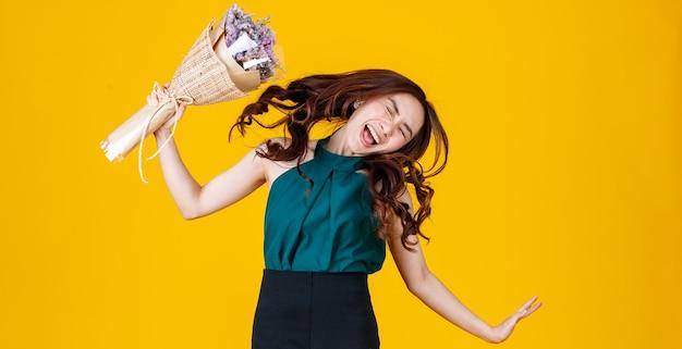 Excitée en amour une femme brune asiatique tenant un bouquet de fleurs saute en l'air avec gaieté et très heureuse. geler l'action d'arrêt avec prise de vue en studio isolée sur fond jaune vif.