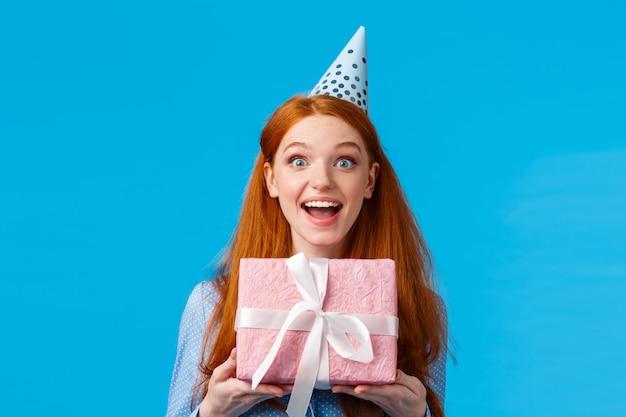 Excitée belle femme rousse glamour aux yeux bleus expression heureuse, recevez un joli cadeau rose, présent enveloppé dans une boîte, souriant amusé, fête son anniversaire en b-day cap