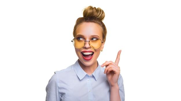 Excitée jeune femme heureuse attirante dans des lunettes avec la bouche ouverte pointant le doigt vers le haut