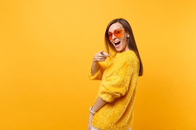Excitée jeune femme en pull de fourrure lunettes coeur orange regardant en arrière pointant l'index sur la caméra isolée sur fond jaune vif. les gens émotions sincères, concept de style de vie. espace publicitaire.