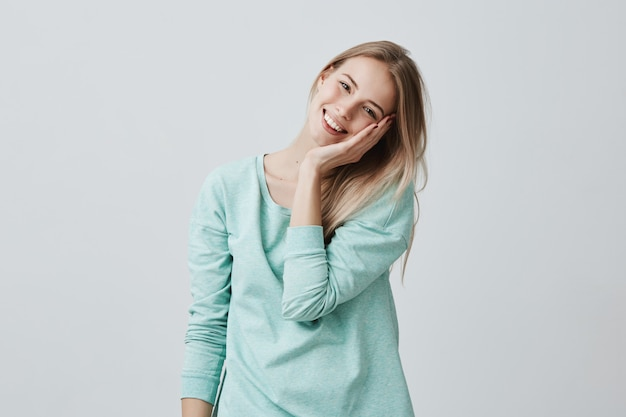 Excitée et ravie belle femme blonde garde la main sur la joue, sourit avec plaisir comme remarque quelque chose d'agréable