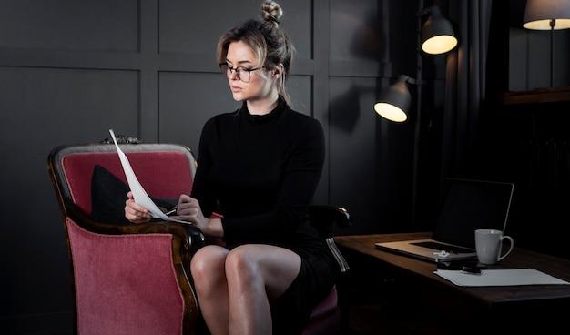 Exécutif moderne jeune femme vérifiant les papiers