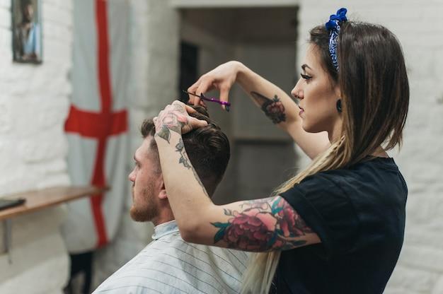 Exécution professionnelle de son robot dans le salon de coiffure de la fille au tatouage