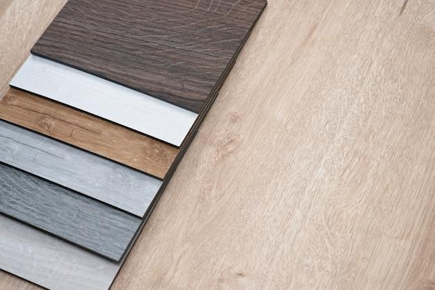 Exemple de catalogue de carreaux de sol en vinyle de luxe avec un nouveau design intérieur pour une maison ou un sol sur une table en bois clair.