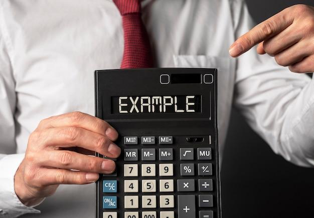 Exemple de mot sur l'affichage de la calculatrice dans les mains des hommes agrandi