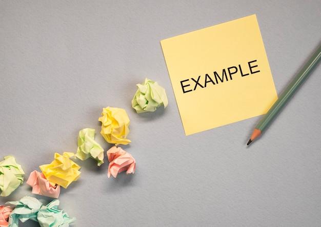 Exemple de mot sur pense-bête jaune sur fond gris avec des papiers froissés