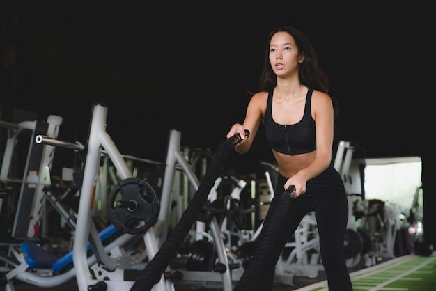 Exercice de crossfit jeune femme fitness avec bataille cordes au gymnase