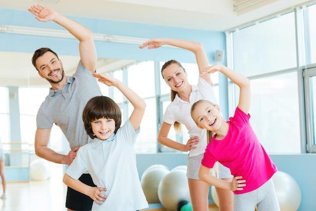 Exercice en famille. heureuse famille sportive faisant des exercices d'étirement dans un club de sport