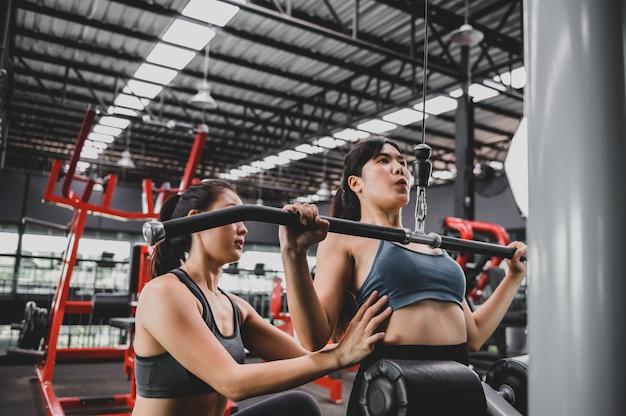 Exercice de femme asiatique et mode de vie à la salle de fitness. entraînement de femme sportive avec entraîneur. bien-être et santé pour la musculation.
