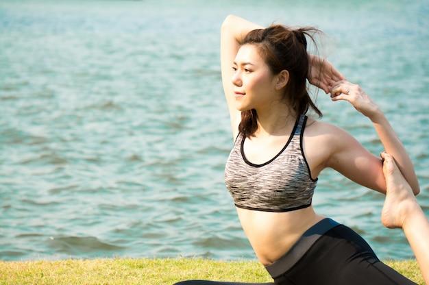 Exercice de femme sport asiatique et étirement par yoga dans le parc