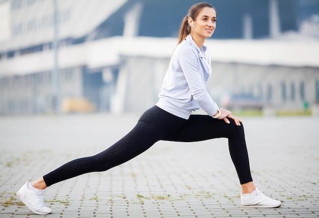 Exercice de fille sportive au parc sur la ville moderne
