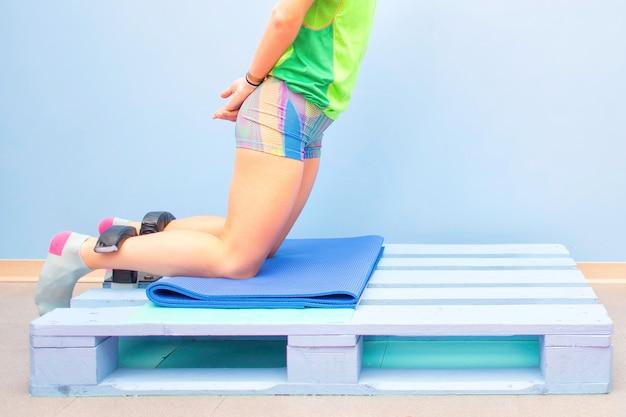 Exercice des ischio-jambiers nordiques sur une palette au gymnase