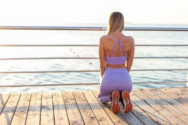 Exercice matinal. jeune femme sportive en tenue de sport pratique la méditation tout en étant assis sur la plage et en regardant le lever du soleil. vue arrière