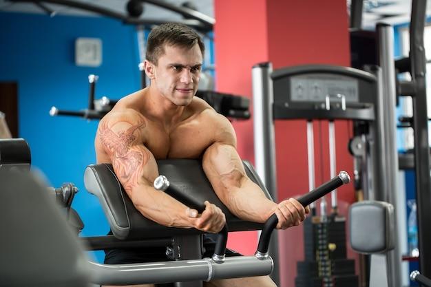 Exercice pour les biceps. jeune culturiste faisant des exercices de poids lourds pour les biceps