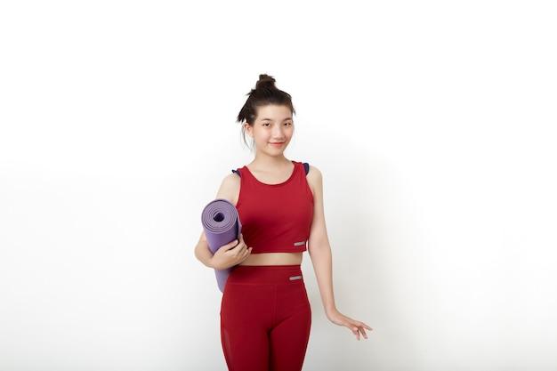 Exercice de remise en forme femme asiatique thaïlandaise prête pour l'entraînement debout tenant un tapis de yoga