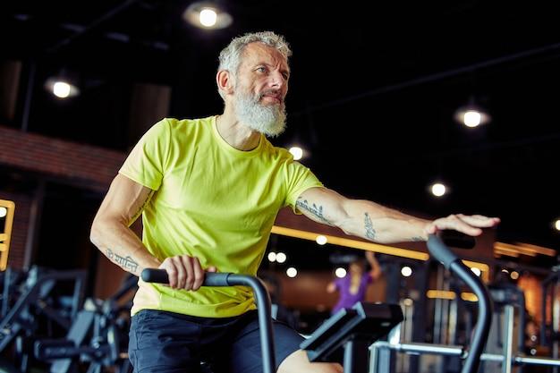 Exercices après vue latérale d'un homme athlétique mature en vêtements de sport faisant du vélo sur des vélos d'exercice à