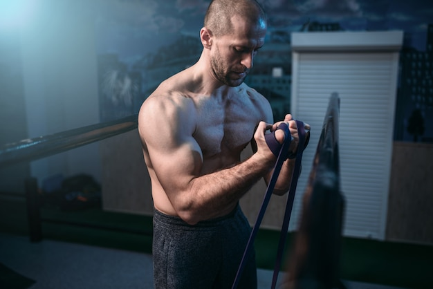 Exercices d'athlète musculaire avec bande élastique. mode de vie sportif actif.