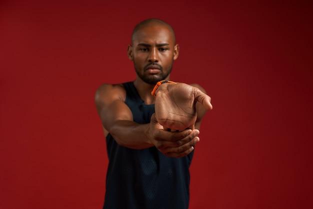 Exercices d'étirement portrait d'un homme afro-américain jeune et fort en vêtements de sport s'étirant