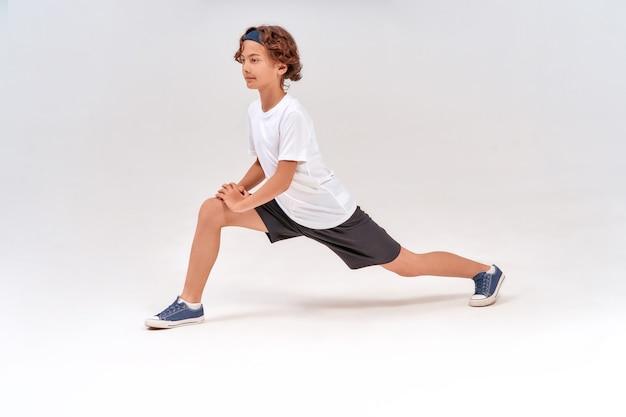 Exercices d'étirement sur toute la longueur d'un adolescent sportif caucasien en vêtements de sport s'échauffant avant