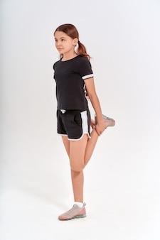 Exercices de gymnastique sur toute la longueur d'une adolescente mignonne en tenue de sport étirant ses jambes en s'échauffant