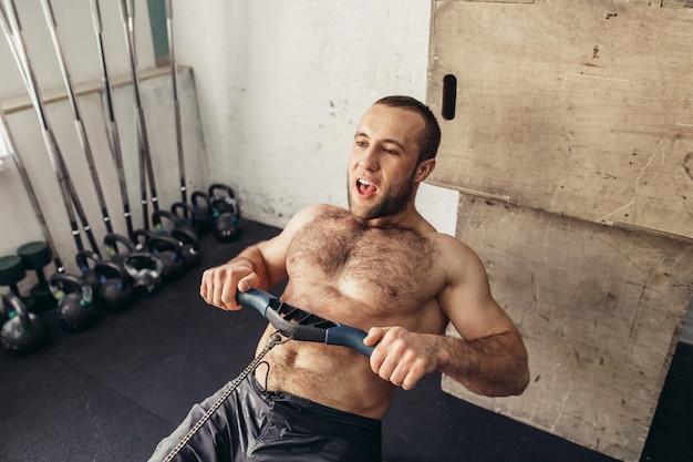 Exercices masculins sportifs fatigués sur la machine d'exercice de puissance dans un club de gym
