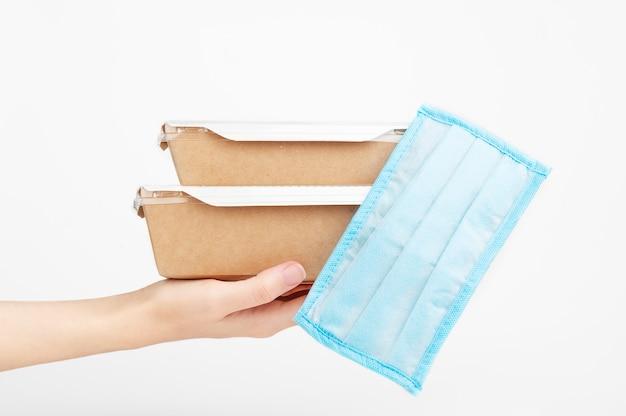 Expédition rapide sans contact. main féminine tenant un carton avec des équipements médicaux de protection.