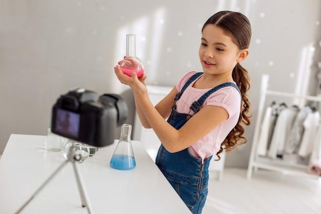Expérience réussie. adorable pré-adolescente montrant une fiole avec un produit chimique rose à la caméra, ayant mené une expérience avec succès, tout en l'enregistrant à la caméra