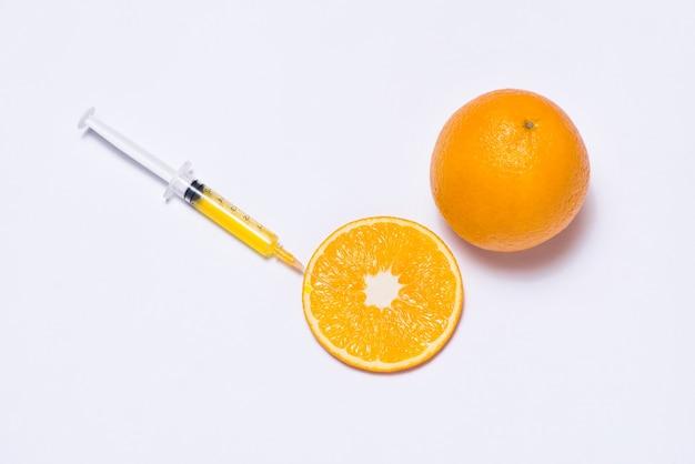 Expérience scientifique avec orange et seringue isolée sur blanc.