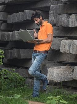 Expert en affaires confiant. confiant jeune bel homme en t-shirt et tenant un ordinateur portable